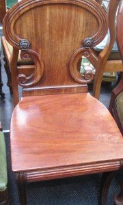 A late Victorian mahogany hall chair having shield back, solid seat and sabre legs.