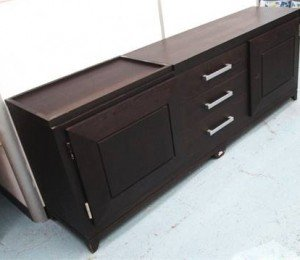 Sideboard with three central drawers flanked by cupboards enclosing shelves.